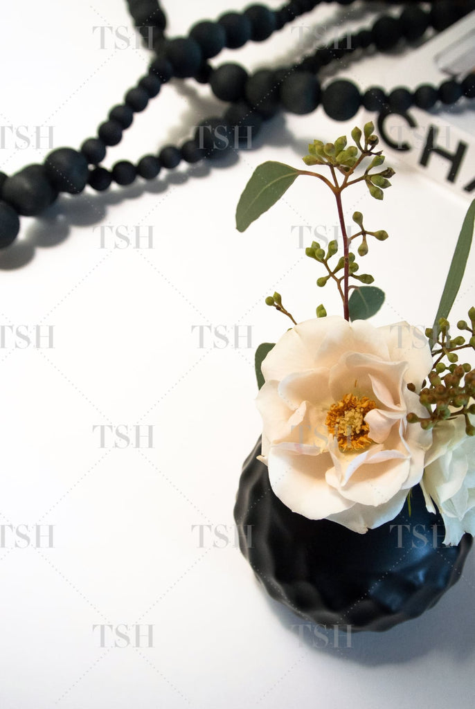 Blush roses in black vase with eucalyptus leaves, fashion book, and decorative black beads on white background.