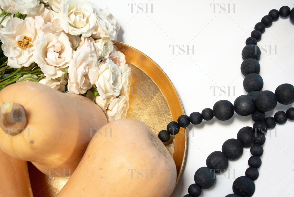 Gold tray with butternut squash, blush roses, and decorative black beads on a white background.