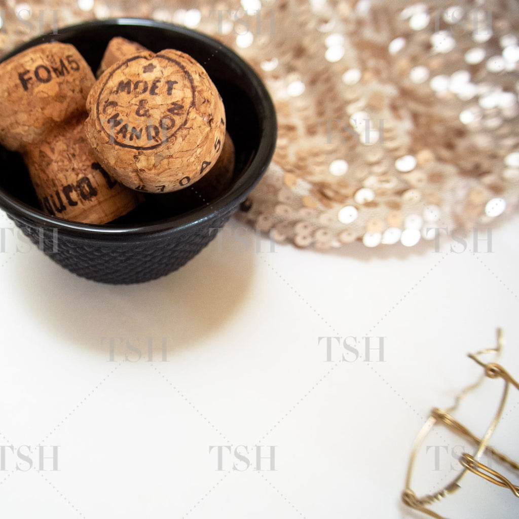 Champagne corks in black bowl with neutral nude sequins on white background.