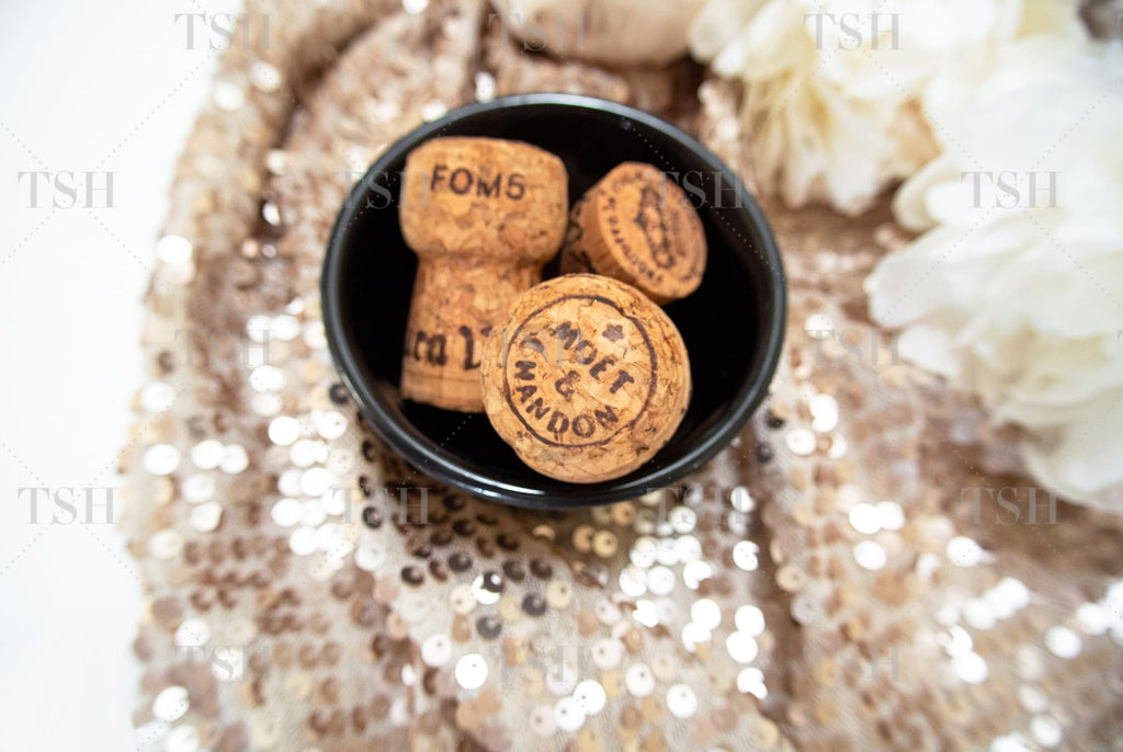 Champagne corks in black bowl and white peony flowers on a neutral nude sequin background.