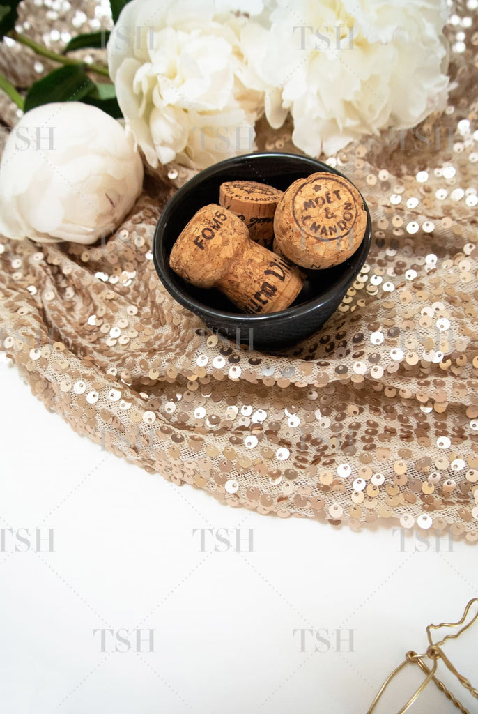 Champagne corks in black bowl and white peony flowers on a neutral nude sequin background