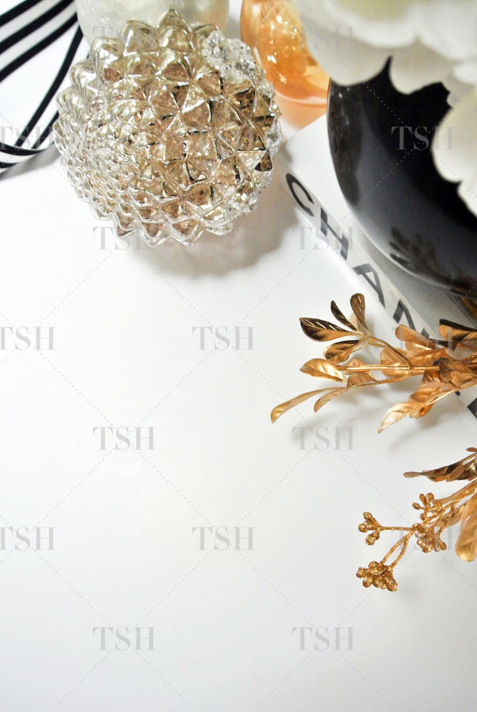 Holiday vignette featuring silver ornaments, gold branches, decorative ribbon, fashion book and black vase with white flowers.