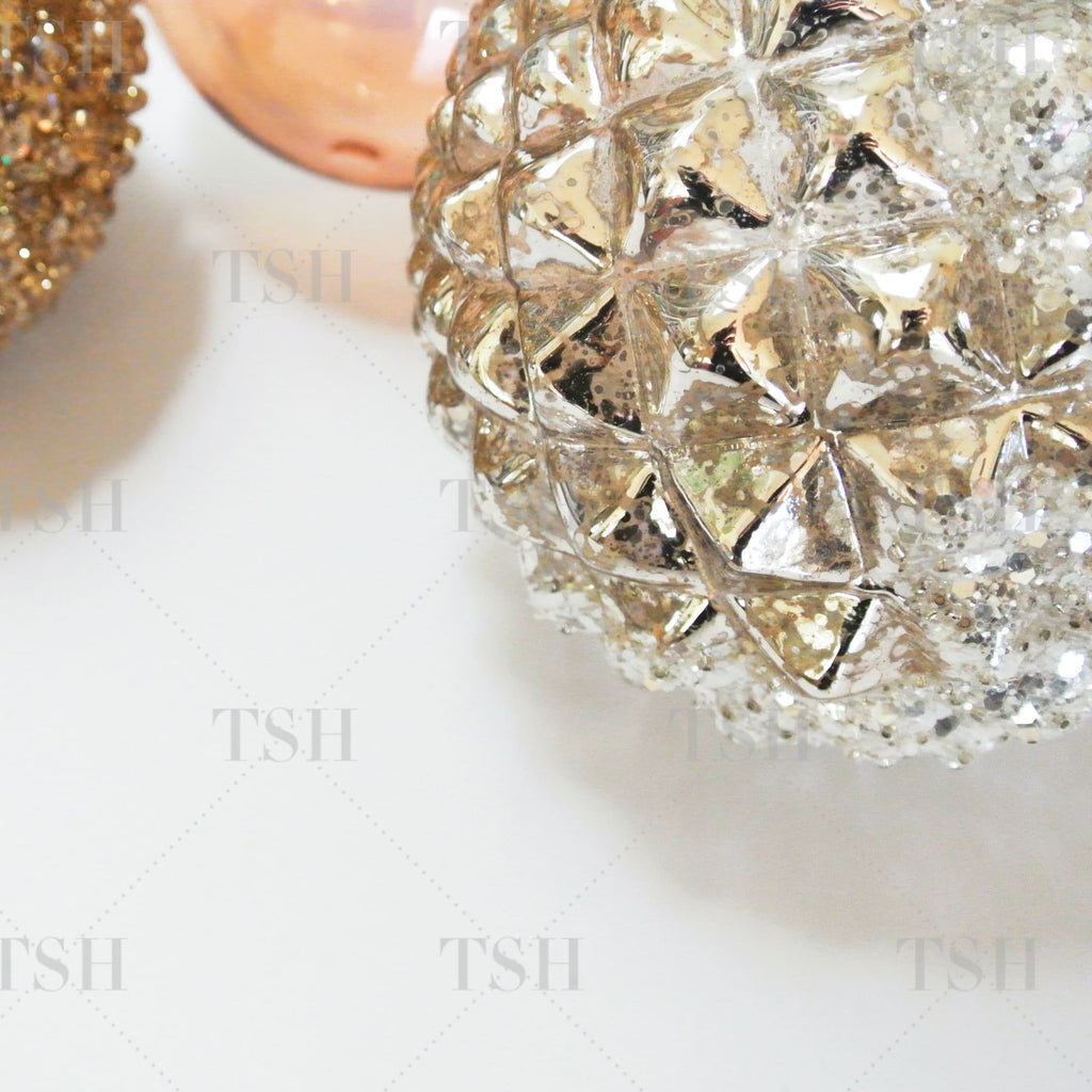 Glamorous and modern holiday assortment of metallic silver and gold ornaments.