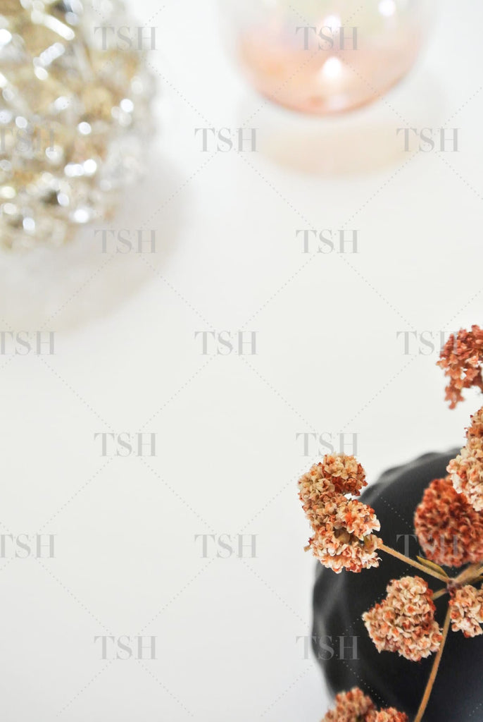 Organic modern holiday assortment of dried flowers in black vase with silver and rose gold ornaments.