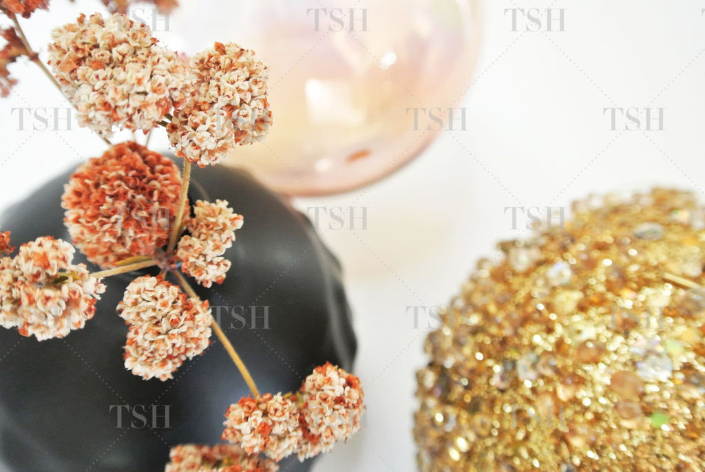 Organic modern holiday assortment of dried flowers in black vase with gold and rose gold ornaments.