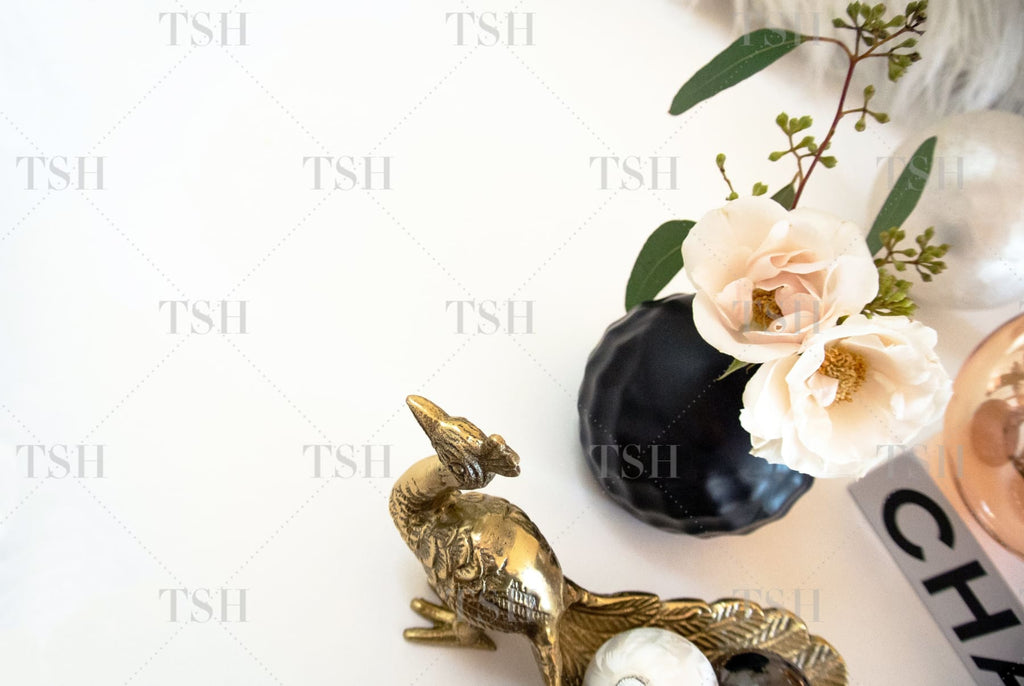 Chic holiday decor with blush roses in black vase, gold peacock, fashion book , and ornaments.