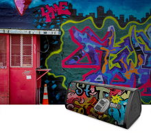 Load image into Gallery viewer, okeegadgets-portable-water-resistant-bluetooth-speaker-black-graffiti-version-graffiti-with-graffiti-wall-in-background