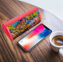 Load image into Gallery viewer, okeegadgets-MIFA-portable-water-resistant-red-bluetooth-speaker-graffiti-version-shown-with-iphone-and-coffee
