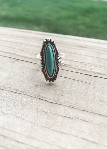 An oval shaped turquoise ring with dainty silver victorian designs and adjustable back from Isac Trading Accessories