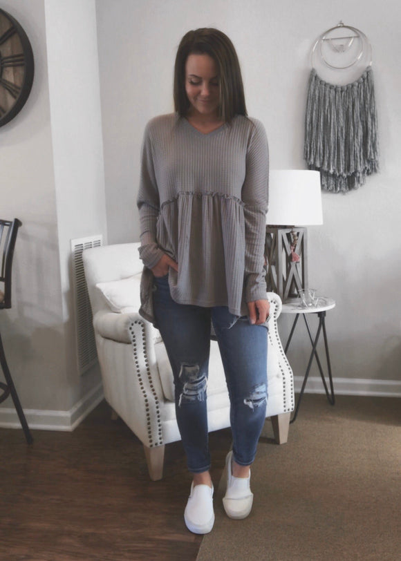 Grey babydoll thermal with long sleeves, a v-neck and ruffle hemlines