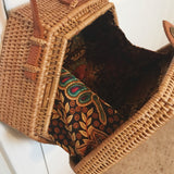 Hand woven, bamboo, rattan bag from Bali with fabric detail inside and a bow tie for closer, with a faux leather strap in a tan or camel color from Etsy