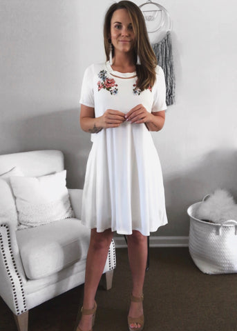 White short sleeve mini dress with a cutout neckline and embroidered flowers from Peach Love California Clothing Apparel