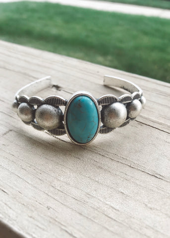 Adjustable matte silver cuff bracelet with oval turquoise stone and accent bulbs