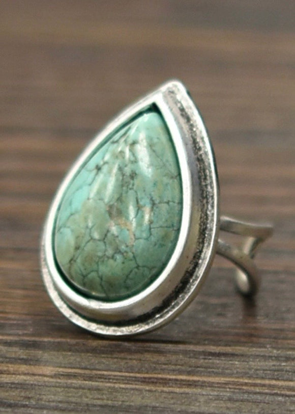 A tear drop shaped turquoise stone ring in a raised silver bezel with an adjustable backing from Isac Trading.