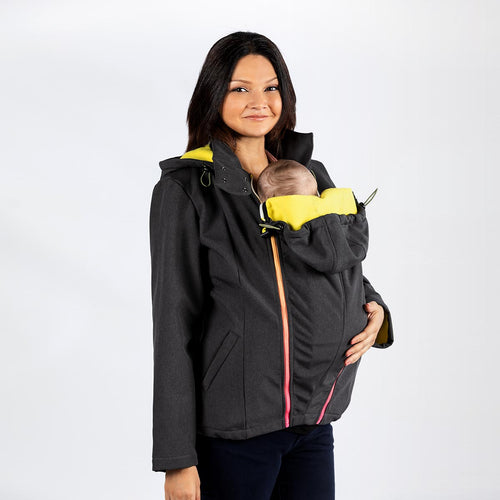 Woman wearing a dark grey babywearing and maternity coat while front carrying a small child.