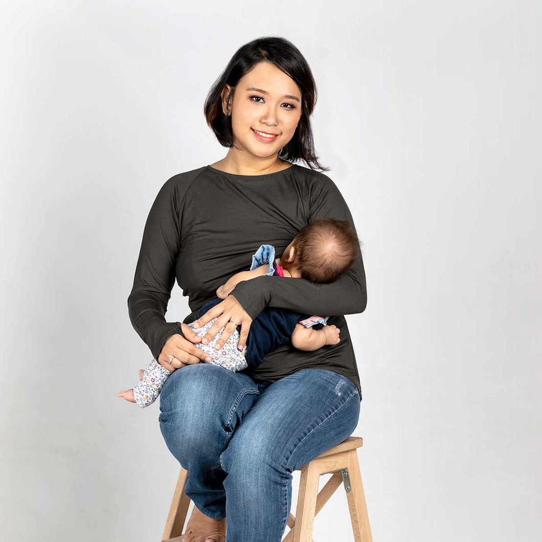 Woman breastfeeding in a dark grey long sleeve nursing top.