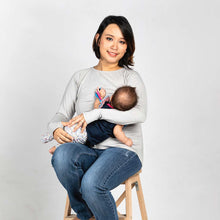 Woman breastfeeding in a light grey long sleeve nursing top.