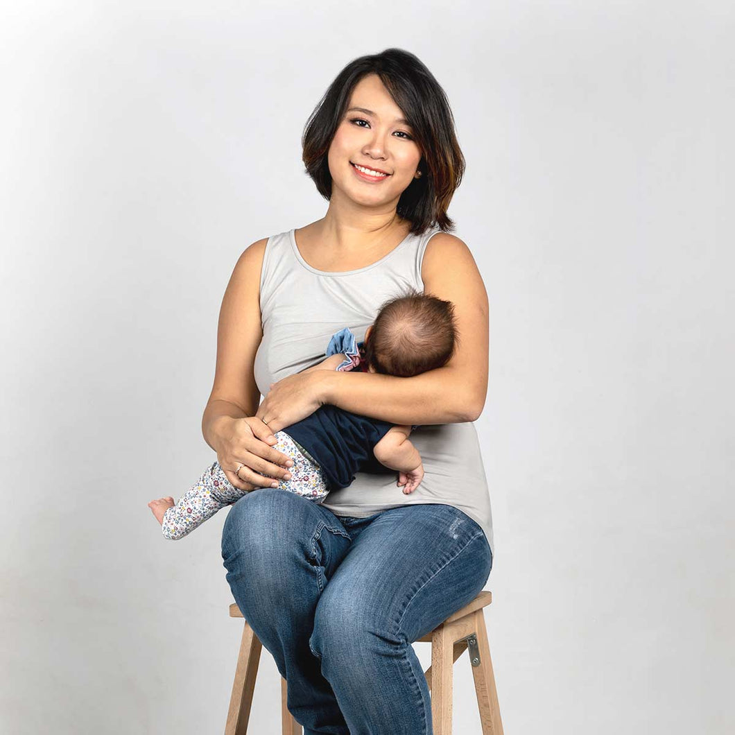 Woman wearing a light grey breastfeeding tank top while breastfeeding an infant.