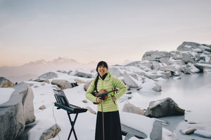 Anastasia Allison of The Musical Mountaineers stands in front of a frozen lake. Photo by Karen Wang.