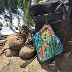 Antimicrobial pee cloth featuring a sloth design by Lyn Sweet. The Kula is attached to a backpack and sitting next to a pair of used hiking boots.