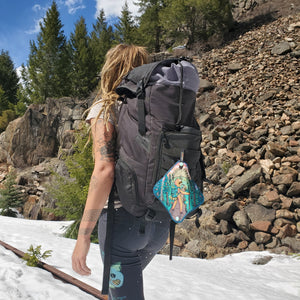 A hiker walking on a trail carrying a backpack. Attached to the backpack is the Adventure Sloth Kula.
