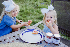 Girls eating Fredericksburg Farms jelly on bread.