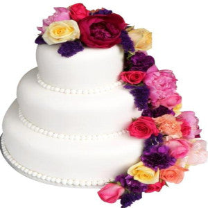 a white colored cake with 3 steps and different colored flowers on the cake of multi color and multi variety  - Expressluv.in