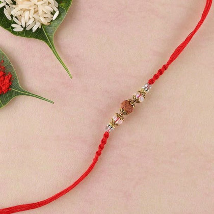 Rudraksha and crystal rakhi with brass beads and red spiral woven thread