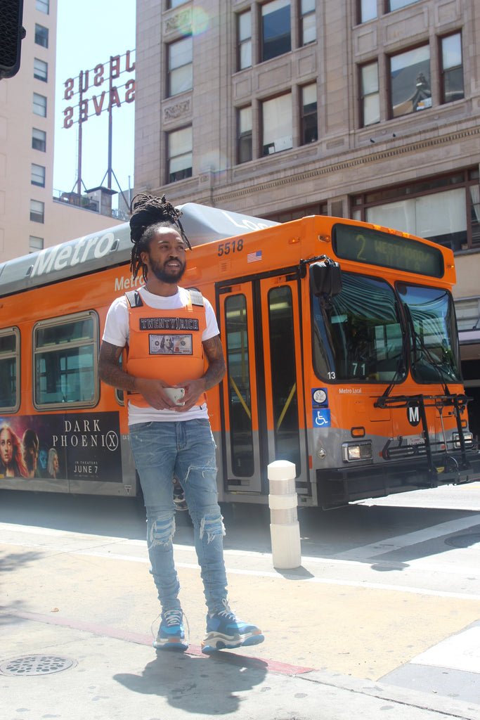 Model wears Orange Vest by Twety1Rich with a $100 logo