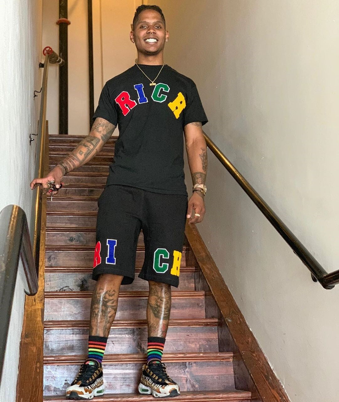 "Male model wears ""RICH"" Tee and Shorts Set by Twenty1Rich with the multicolored ""RICH"" logo"