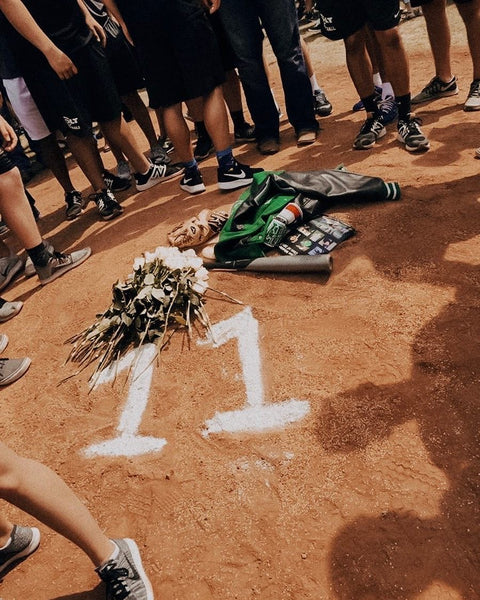 A group of high schoolers gathered around the number 11 written in line chalk on the pitcher's mound.