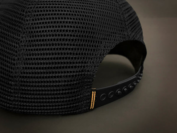 Back of trucker hat featuring black mesh and black snap closure.