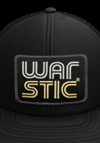 "Close up of front of black trucker style hat with white patch that says ""Warstic"" in white and gold."