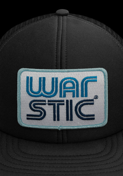 "Close up of front of black trucker style hat with white patch that says ""Warstic"" in royal blue and navy."