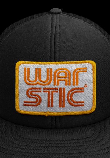 "Close up of front of black trucker style hat with white patch that says ""Warstic"" in sun yellow and fire orange."