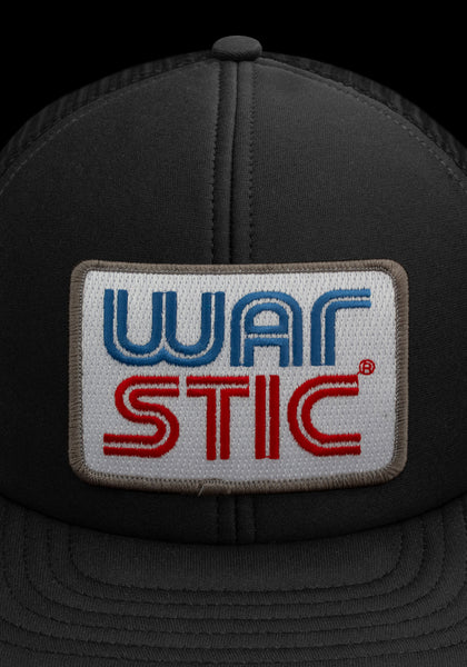 "Close up of front of black trucker style hat with white patch that says ""Warstic"" in royal blue and blood red."