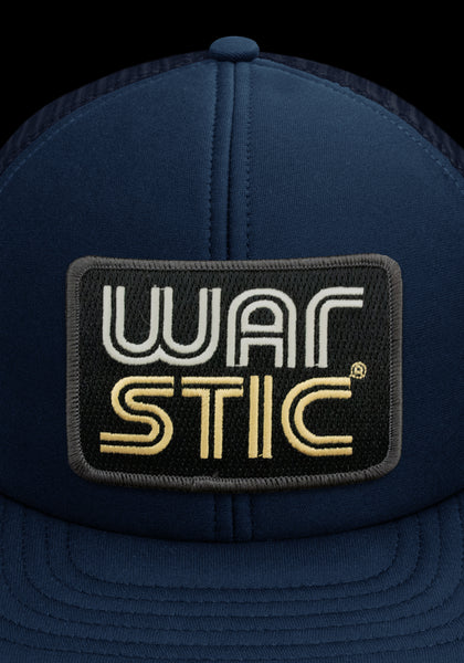 "Close up of front of navy trucker style hat with box patch that says ""Warstic"" in white and gold."
