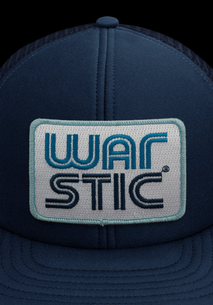 "Close up of front of navy trucker style hat with white patch that says ""Warstic"" in royal blue and navy."