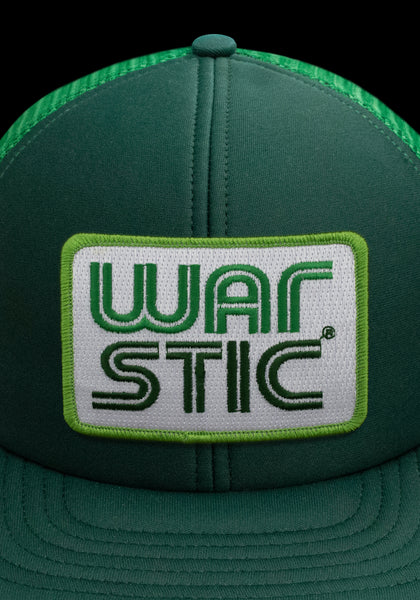 "Close up of front of green trucker style hat with white patch that says ""Warstic"" in grass green and forest green."