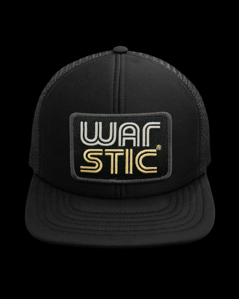 "Front of black trucker style hat with black patch that says ""Warstic"" in white and gold."