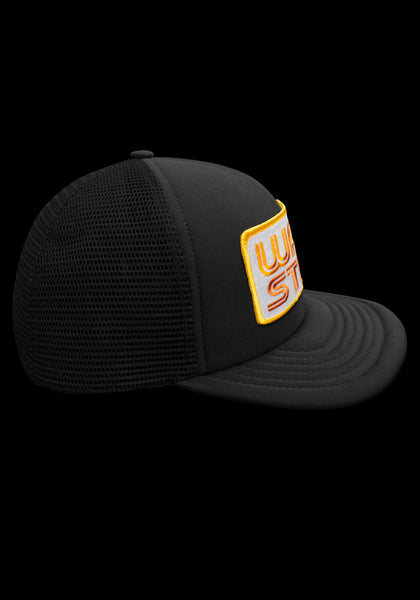 "Side view of black trucker style hat with white patch that says ""Warstic"" in sun yellow and fire orange."