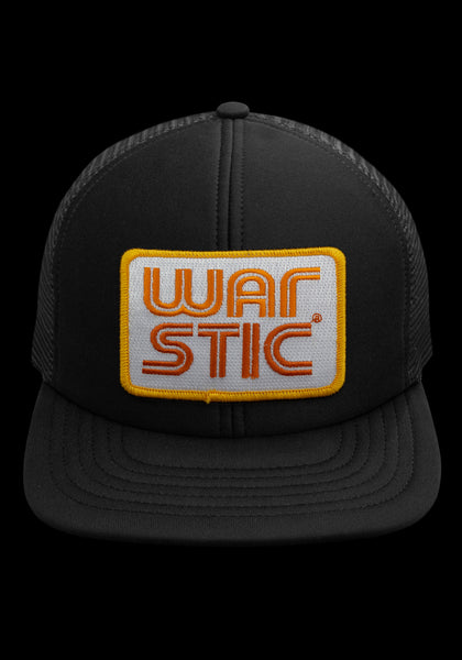 "Front of black trucker style hat with white patch that says ""Warstic"" in sun yellow and fire orange."