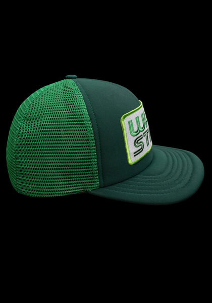 "Side view of green trucker style hat with white patch that says ""Warstic"" in grass green and forest green."