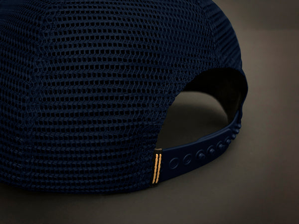 Back of trucker hat featuring navy mesh and navy snap closure.