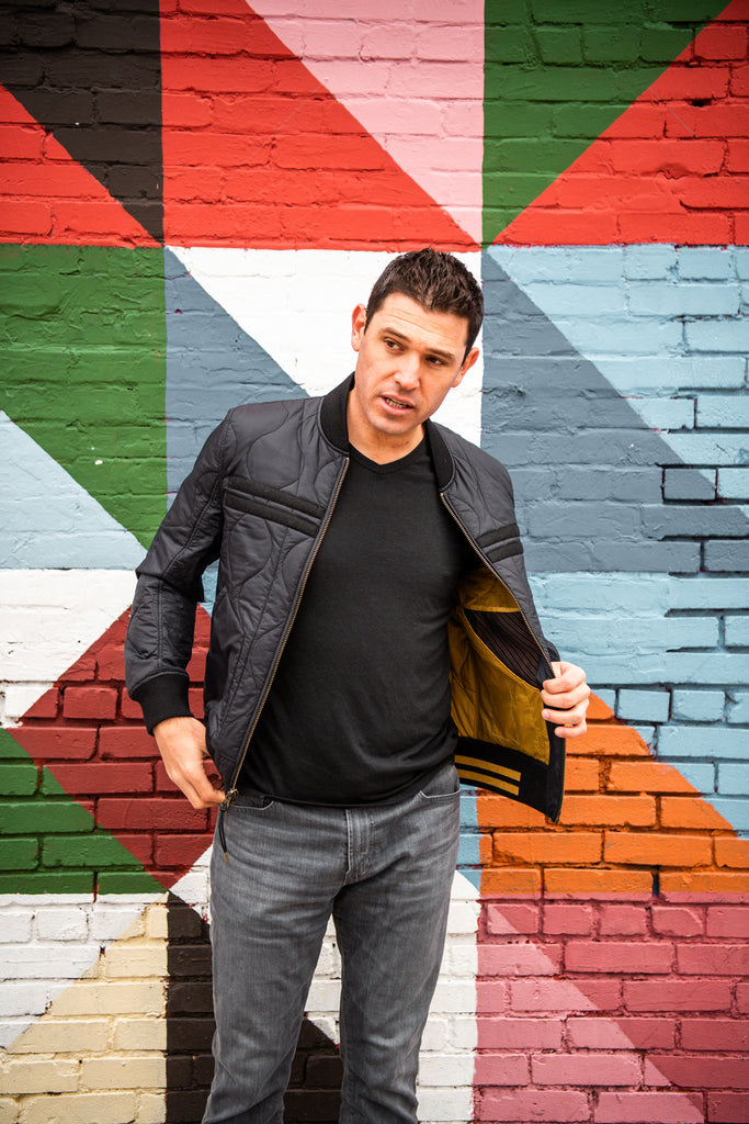 Warstic co-owner Ian Kinsler wearing the Warstic x Billy Reid Icon Player's Jacket in front of a multi-colored mural