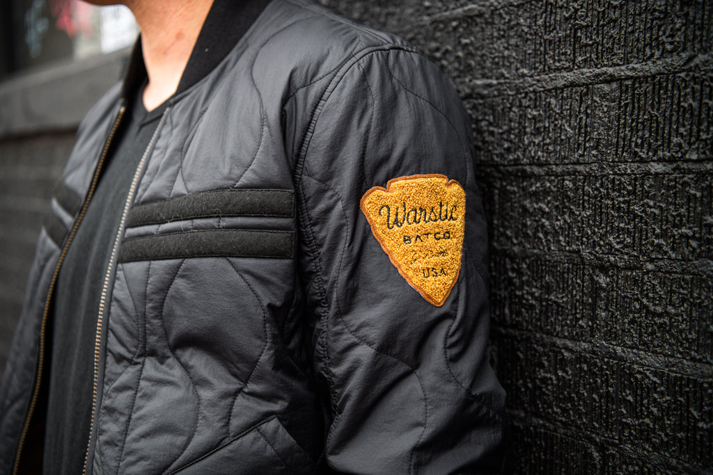 View of the front of the jacket, showing the detail of the black on black warstripes and the goldenrod Warstic Arrowhead logo chenille patch on the left shoulder.