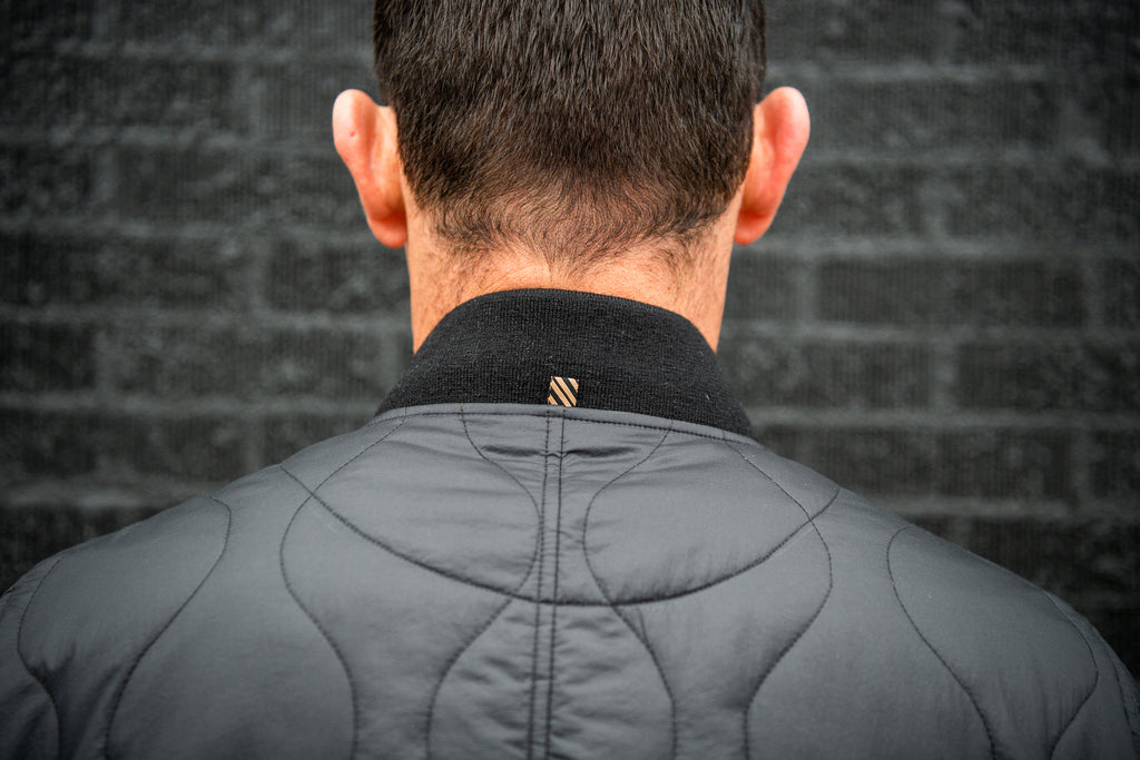 View of the back of the Warstic x Billy Reid Icon Player's Jacket, with a tab of Billy Reid's signature ribbon fabric stitched at the collar.