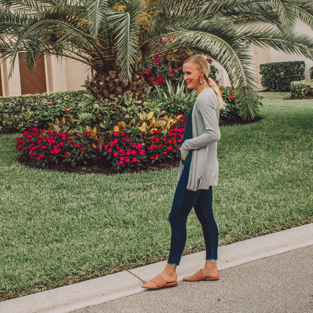 A grey long sleeve cardigan with blue jeans and tan slider mules.