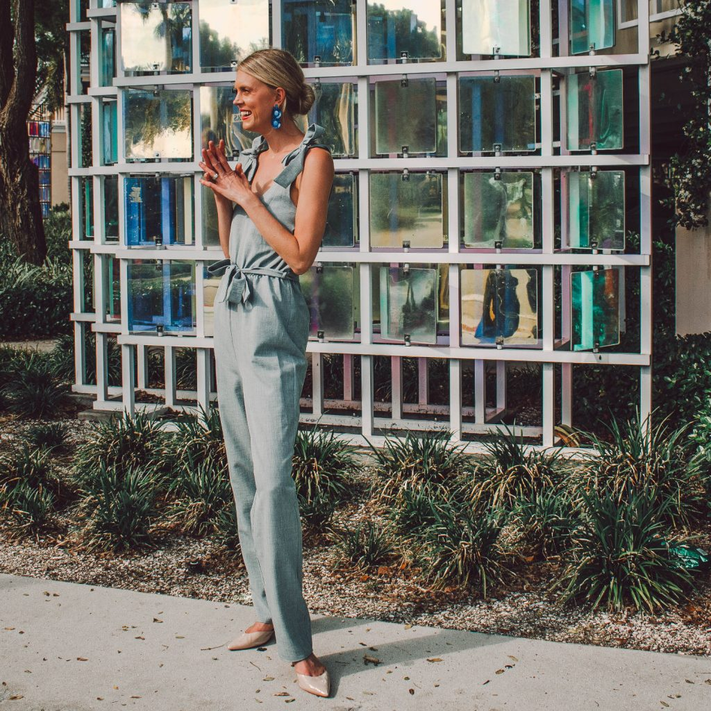 A chambray jumpsuit with tie shoulders and a tie waist, paired with a pointed toe heel.