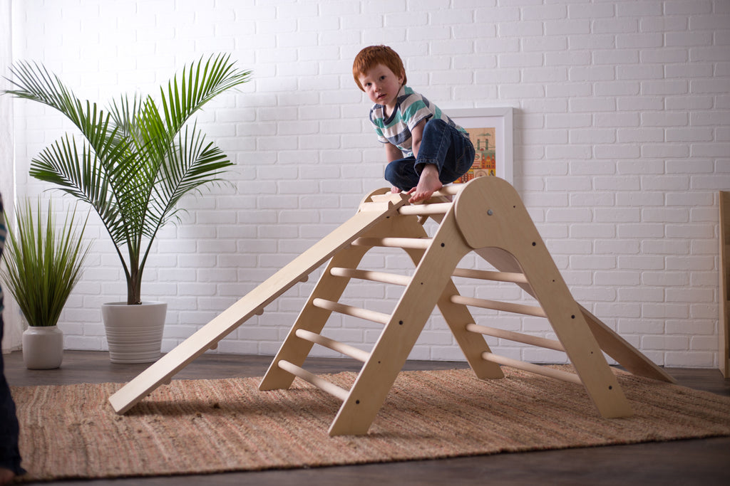 A child looks out from the top of his Pikler Triangle.